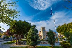 Volos, Magnisia, Hellas, Greece - April 2017. Stone Church of the Annunciation with the city clock on the tower on the Evaggelistrias Square among the beautiful Stock Photo