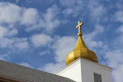 Stone church with gold dome steeple against blue skies. Stone and brick church with gold dome steeple against blue skies Stock Photos