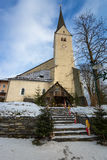 Stone church with high belfry in Austrian Alps Stock Photos
