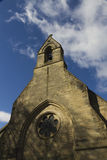 Stone church with open bell tower against blue sky and cloud. Stock Photo