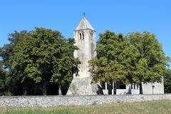 Stone church tower behind tall trees Stock Images