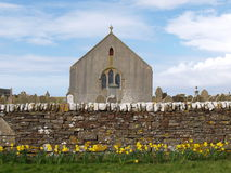 Stone Church and Wall. Small stone church with graveyard behind a stone wall with yellow flowers in front, shot in the Orkney Islands, Scotland royalty free stock images