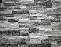 Stone cladding wall made of faux stone bricks with black, gray and white colors. stock images