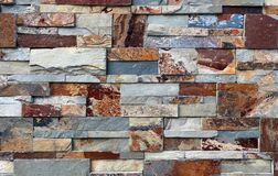 Free Stone Cladding Wall Made Of Natural Stones Of Different Shapes. The Main Colors Are Red, Gray,orange And Brown. Royalty Free Stock Photo - 186031145