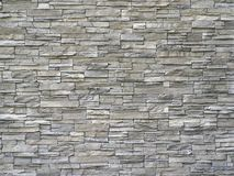 Stone cladding wall made of  striped stacked slabs of natural gray rocks. Panels for exterior . stock photos