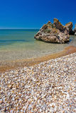 Stone cliff on the sea coast with shells. And blue sky stock photo