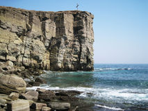 A stone cliff in the sea. Cross on a rocky cliff in the sea Royalty Free Stock Photography