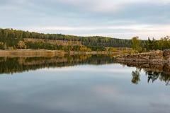 A stone cliff surrounds the lake shore Fall Stock Photo