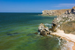 Stone cliffs on the coast and blue sky with clouds Stock Photo