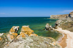 Stone cliffs on the coast and blue sky with clouds Stock Images