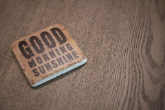 A stone coaster on a wooden table surface reading Good Morning Sunshine. Stone coaster on a wooden table surface reading Good Morning Sunshine Royalty Free Stock Images