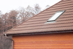 Stone Coated Metal tile Roof with skylights and rain gutter. Royalty Free Stock Image