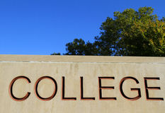 Stone College Sign with tree. Stone carved sign for an institution of higher learning (college or university) with blue sky background and tree royalty free stock photography
