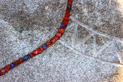 Stone with colored stones. On the rock extends a curved line of small stones Stock Photography