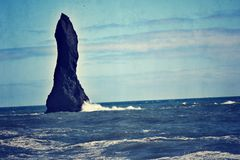 Stone column in iceland. A stone column in iceland in the ocean at the black sand beach in southern iceland Stock Image