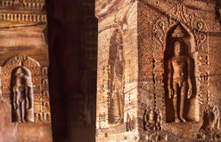 Stone columns with carved Bahubali meditating, sculpture depicting hero of Jainism inside the 7th century cave Stock Photos