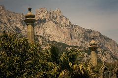 Stone Columns in Park of Vorontsov Palace in Crimea. Panorama of high stone columns in park of Vorontsov palace against rocky hill in Crimea Ukraine royalty free stock photo