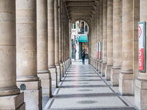 Stone columns and tiled floor arcade outside Comedie Francaise,. Paris, France, Sept 5, 2015: woman walks to end of covered arcade of tiled floors and stone Royalty Free Stock Image