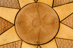 Stone compass rose set within a star. Golden coloured paving sla Royalty Free Stock Photo