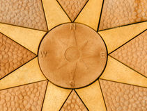 Stone compass rose set within a stone  star. Golden coloured paving sla Royalty Free Stock Images