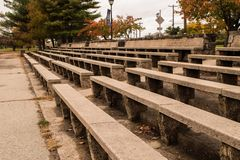Stone and concrete bleachers in a park. Long concrete benches with stone bases set up like bleachers with trees in background royalty free stock photos