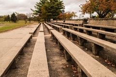 Stone and concrete bleachers in a park. Long concrete benches with stone bases set up like bleachers with trees in background royalty free stock photo