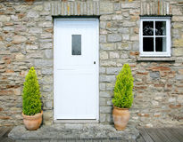 Stone cottage door. Old stone cottage with white stable door and small window to the side, two small conifers in terracotta pots either side of the door Stock Photography