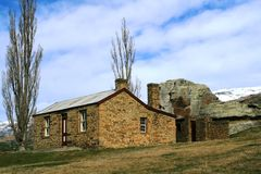 Stone Cottage on the Hill. An historic stone cottage and outbuildings located in the middle of a paddock that is grazed by animals.  Lovingly restored to their Royalty Free Stock Image