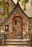 Stone Cottage. Retro stone cottage with wooden door and red trim Stock Photo
