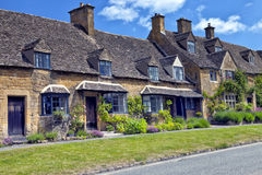 Stone Cottages in rural English village by a road Royalty Free Stock Photos