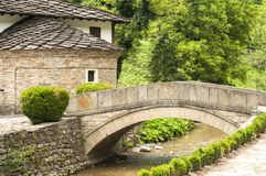 Stone countryhouse and stone bridge. Old stone country house and stone vaulted bridge over small river Stock Photography