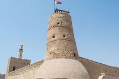 Stone cream colour ancient arabic fort with tower and high walls. In the UAE Stock Images