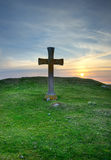 Stone cross. With the sun going down in the background Royalty Free Stock Photography
