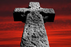 Stone cross. At dark red sunset sky Royalty Free Stock Photos
