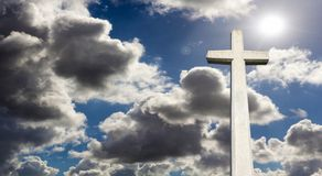 Stone cross agaist blue cloudy sky. Stone cross against blue sky with dark clouds and sunlight Stock Photography