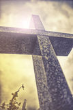 Stone cross against dramatic cloudy sky, vintage effect Royalty Free Stock Images