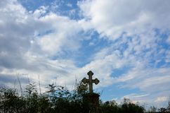 Stone cross with blue dramatic. Stone cross with blue dramatic sky and clouds on brick stand Royalty Free Stock Image