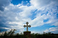 Stone cross with blue dramatic sky and clouds Royalty Free Stock Images