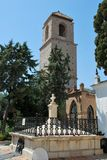 Stone cross & castle tower, Alora, Spain. Remnants of now defunct cemetery with tower to rear, Castle del Cerro de las Torres, Alora, Malaga Province, Andalusia Stock Image