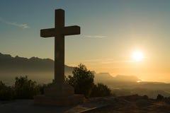 Stone cross. Christian stone cross under the warm light of sunrise Royalty Free Stock Photography
