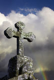 Stone Cross in a cloudy sky. And rainbow Stock Image