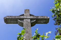 Stone cross on deep blue sky. Old stone christian cross on a bright sunny day. Ave crux, spes unica is a Latin pious expression or motto meaning Hail to the Royalty Free Stock Image