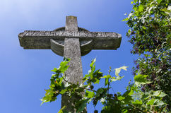 Stone cross on deep blue sky. Old stone christian cross on a bright sunny day. `Ave crux, spes unica` is a Latin pious expression or motto meaning `Hail to the Royalty Free Stock Photos