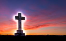 Glow of Hope Cross. Stone cross with a glow around it, on a hill area with a wonderful dawn morning sky royalty free stock images