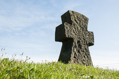 Stone cross on grass with a blue sky Royalty Free Stock Photo