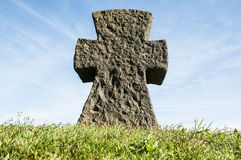 Stone cross on grass with a blue sky Royalty Free Stock Photos