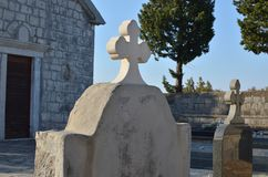 Stone cross of a grave. With a small village church facade behind it Stock Images