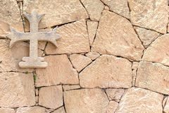 Stone cross hanging on a stone wall, background.  Stock Photos