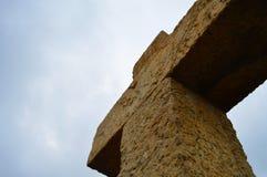 Stone cross. A heavy, big stone cross pointing to the sky Royalty Free Stock Photo