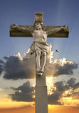 Stone cross with Jesus and sky with sunbeams Royalty Free Stock Photos